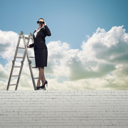 businesswoman climbed a ladder and looking through binoculars photo