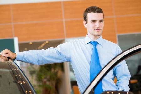dealerships: dealer stands near a new car, car dealerships