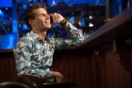 man talking on the phone while sitting with a cup of coffee at the bar photo