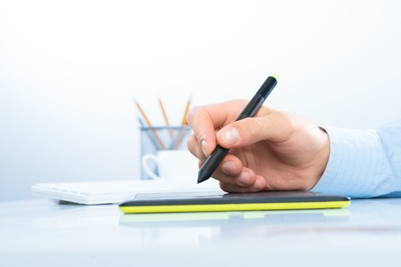 peripherals: Designer hand drawing a graph on the tablet which lies on a white table Stock Photo