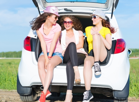 young attractive woman sitting in the open trunk of a new car, a summer road trip photo