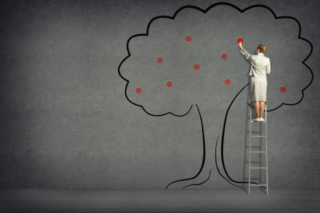 business woman standing on a ladder and touches of tree painted on the wall photo