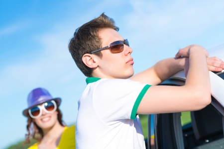 young man in sunglasses standing next to the car, the summer road trip photo