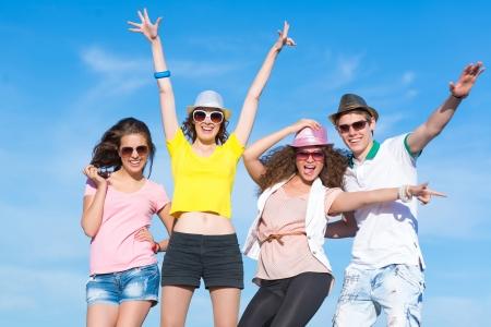 fiesta familiar: Grupo de j�venes que se divierten en un cielo azul de verano Foto de archivo