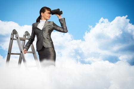 zakenvrouw klom een ladder en kijkt door een verrekijker Stockfoto