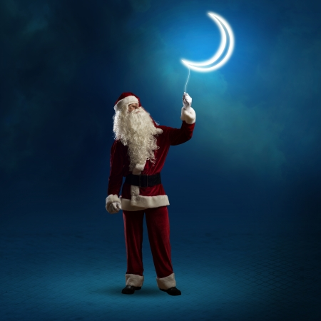 Santa Claus holding a string of luminous glowing moon photo