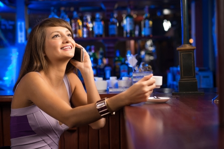 woman talking on the phone while sitting with a cup of coffee at the bar photo
