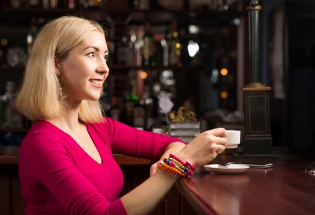 woman with a cup of coffee at the bar photo