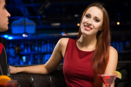 Portrait of an attractive woman in a nightclub, sitting on the couch with a drink photo
