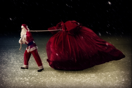 Santa Claus in a night pulling a huge bag of gifts photo