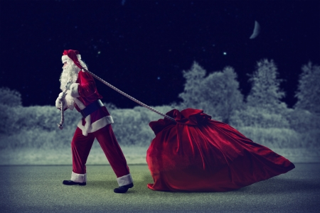 Santa Claus in a night winter forest pulling a huge bag of gifts photo
