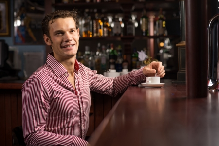 man with a cup of coffee at the bar photo