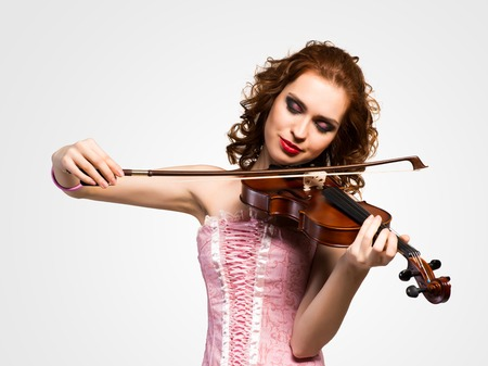 young attractive woman in pink corset on a violin, closed her eyes and smiles photo