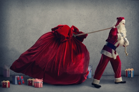 Santa Claus pulls a huge bag of gifts lying around boxes with gifts Stock Photo