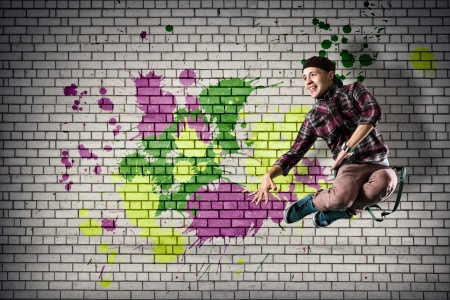young male dancer jumping behind a wall covered in paint