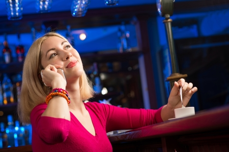 portrait of a young woman in a bar with a cell phone and a cup of coffee photo