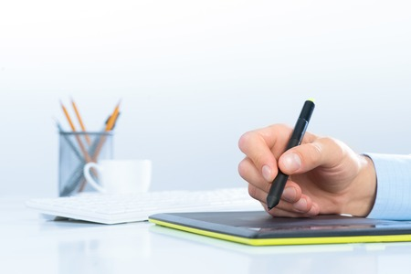 Designer hand drawing a graph on the tablet which lies on a white table photo