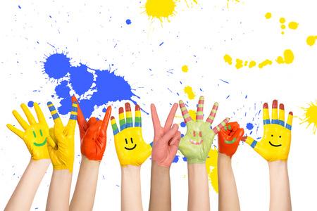 trekken: geschilderd kinderen handen in verschillende kleuren met smilies Stockfoto