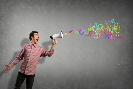 Portrait of a young man shouting using megaphone, of the horn fly, abstract symbols photo