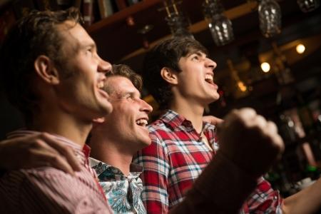 세 남자는 미소를 포용하는 행에 서 있고, 당신의 앞에 스포츠 팬을 찾아