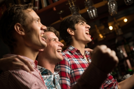 football party: Three men stand in a row embracing smile and look in front of you, sports fans
