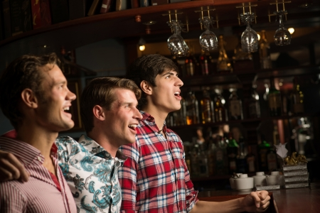 sports bar: Three men stand in a row embracing smile and look in front of you, sports fans