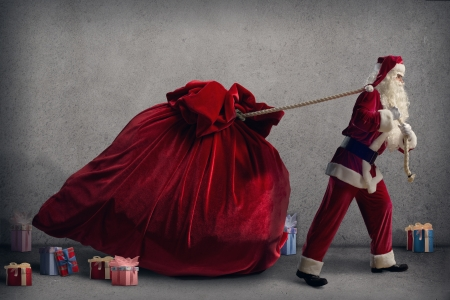 Santa Claus pulls a huge bag of gifts lying around boxes with gifts photo