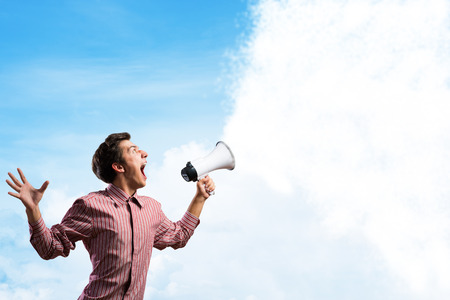 Portrait of a young man shouting using megaphone, of the horn fly clouds photo