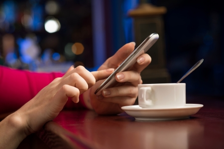 close-up of female hands holding a cell phone, sitting at the bar, next to a cup of coffee photo