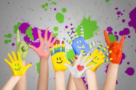 Manos de los niños pintados s en diferentes colores con emoticones Foto de archivo - 24512128