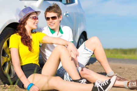 young couple sitting on the ground next to the wheel of a car, a summer road trip photo
