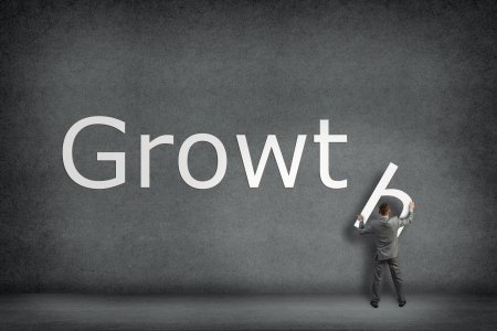 Businessman collects on the wall the word growth, places the letter on the wall Stock Photo - 24535989