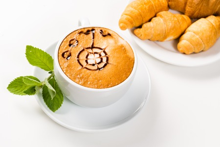 large cup of coffee with a pattern on foams and croissants on a plate, an early breakfast photo