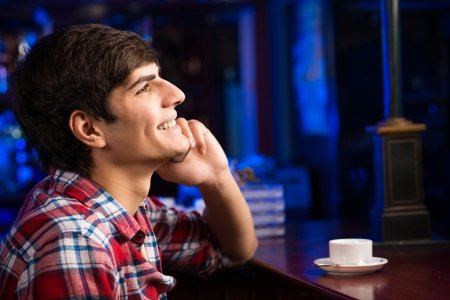 young man at the bar on the phone and drinking coffee photo