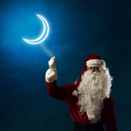 Santa Claus holding a shining light symbol of the moon for thread photo