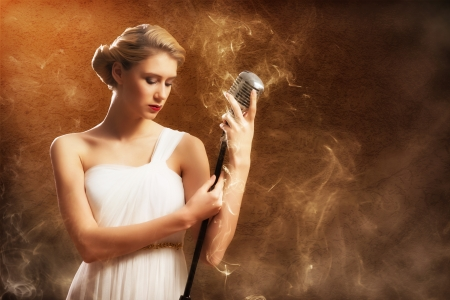 beautiful blonde woman singer with a microphone, eyes closed, around smoke photo
