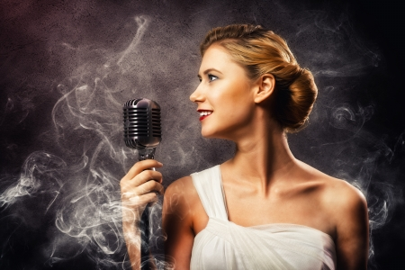 beautiful blonde woman singer with a microphone, eyes opened, around smoke photo