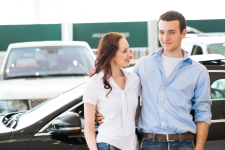 purchasers: Young couple standing embracing near a car in the showroom