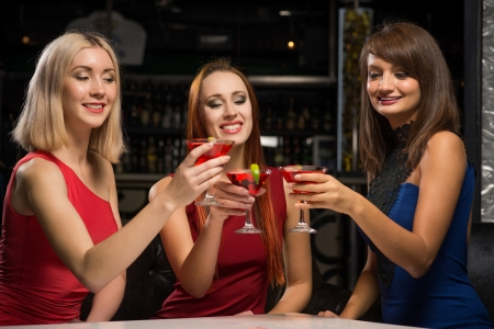 three girls raised their glasses in a nightclub, have fun with friends photo