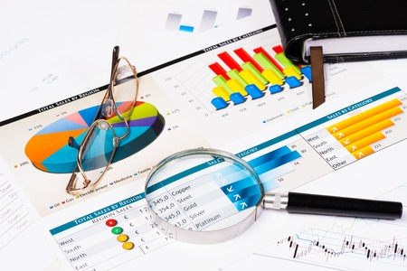 Tagebuch, Brille, Lupe und Geschäftsdokumente mit Diagrammen, Business-Stillleben