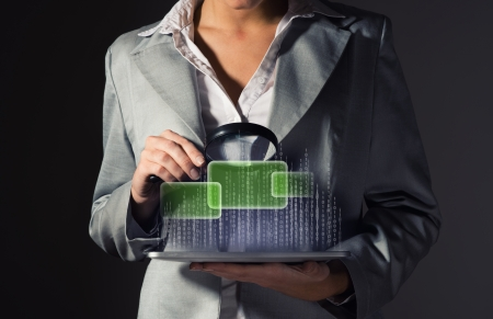 business woman looks at the binary code of the tablet computer, the concept of information security photo