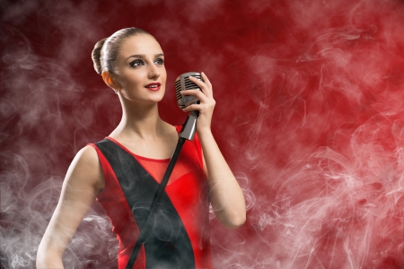eyes opened: beautiful blonde woman singer with a microphone, eyes opened, around smoke Stock Photo