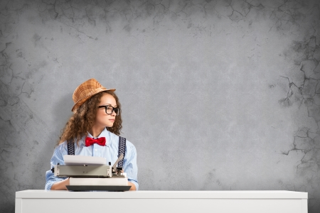 image of a young woman writer at the table with typewriter