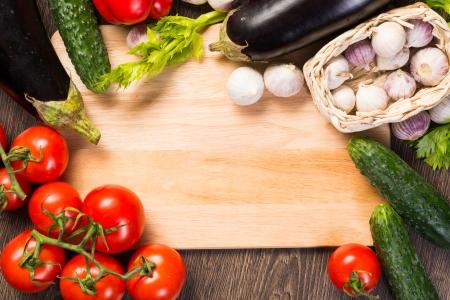 tomatoes, cucumber, garlic, fresh herbs on chopping board photo