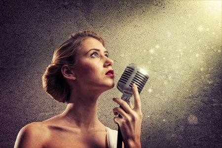female singer: attractive female singer with a microphone behind her abstract background Stock Photo