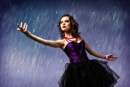 Young woman dancing in the rain, held up his hand and looks at it photo