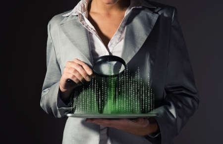 business woman looks at the binary code of the tablet computer, the concept of information security