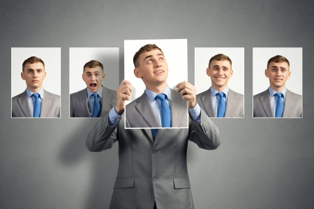 additional: young man holds up a photograph hanging on the wall behind the additional photos with different emotions Stock Photo
