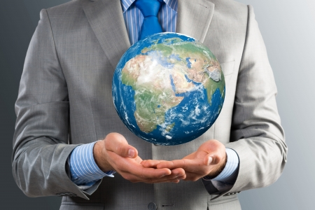 businessman carrying a globe: businessman holds up a planet   Stock Photo
