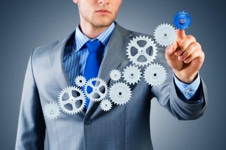 businessman touch the mechanism, run a successful business concept photo